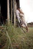 Couples heureux flirtant par espièglerie dehors contre le mur de grange Photographie stock