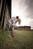 Couples heureux flirtant par espièglerie dehors contre le mur de grange Photos libres de droits