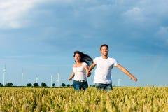 Couples heureux fonctionnant au-dessus du grainfield Images libres de droits