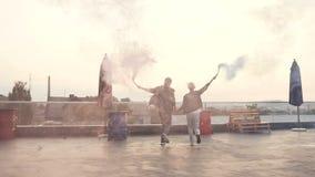 Couples heureux fonctionnant avec de la fumée colorée sur le toit de terrasse du bâtiment moderne Jeunes ajouter de hippie à colo clips vidéos