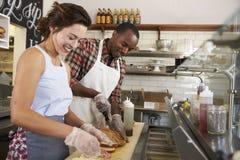 Couples heureux fonctionnant derrière le compteur à une barre de sandwich image libre de droits