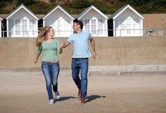 Couples heureux fonctionnant en bas de la plage Photos libres de droits