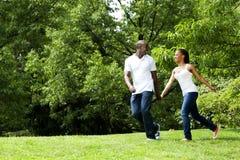 Couples heureux fonctionnant en stationnement Image libre de droits