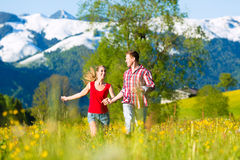 Couples fonctionnant dans le pré avec la montagne image stock