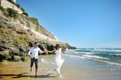 Couples heureux fonctionnant sur la plage près de la mer dans le jour du mariage Photos stock