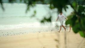 Couples heureux fonctionnant sur la plage Voyage ensemble banque de vidéos