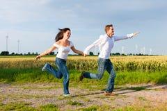 Couples heureux fonctionnant sur un chemin de terre en été Photos stock