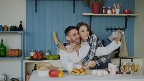 Couples heureux gais ayant la causerie visuelle en ligne utilisant le smartphone dans la cuisine à la maison pendant le matin Photo stock