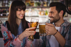 Couples heureux grillant des verres de bière au compteur Images stock