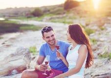 Couples heureux grillant le vin mousseux de champagne à une partie de détente Photos stock