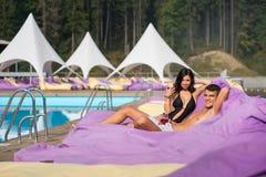 Couples heureux - homme et femme détendant près de la piscine sur les canapés amortis avec des boissons au lieu de villégiature l Photos libres de droits