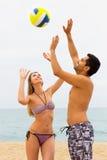 Couples heureux jouant avec une boule à la plage Images stock