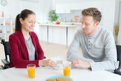 Couples heureux jouant des cartes à la maison qu'elle a désactivées Photographie stock libre de droits