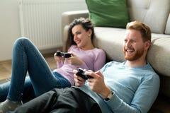 Couples heureux jouant des jeux vidéo à la maison Photo libre de droits