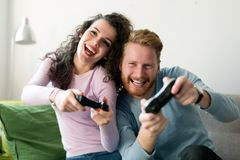Couples heureux jouant des jeux vidéo à la maison Images stock