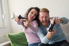 Couples heureux jouant des jeux vidéo à la maison Photos stock