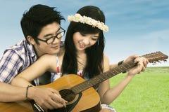 Couples heureux jouant la guitare Images libres de droits