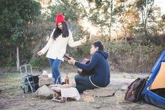 Couples heureux jouant la guitare dans la saison d'hiver de nature image stock
