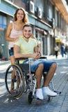 Couples heureux à la promenade de fauteuil roulant par la ville Image stock