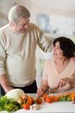 Couples heureux mûrs faisant cuire à la cuisine images stock