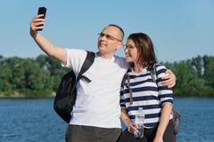 Couples heureux mûrs prenant la photo de selfie au téléphone, les gens détendant près de la rivière en parc de soirée d'été image stock