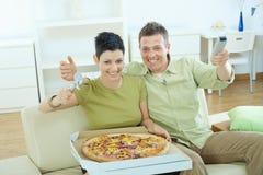 Couples heureux mangeant de la pizza Images stock