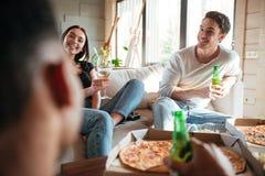 Couples heureux mangeant de la pizza, de la bière potable et du vin avec des amis Images stock