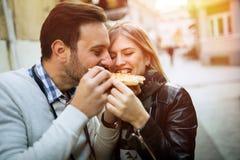 Couples heureux mangeant de la pizza dehors Photographie stock libre de droits