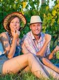 Couples heureux mangeant des raisins dans le vignoble Photo libre de droits