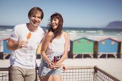 Couples heureux mangeant la balustrade se tenante prêt de crème glacée à la plage Photo stock