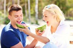 Couples heureux mangeant la pastèque à la plage Image libre de droits