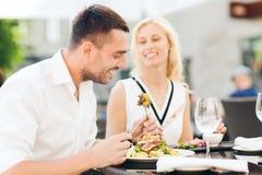 Couples heureux mangeant le dîner à la terrasse de restaurant Photos libres de droits