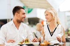 Couples heureux mangeant le dîner à la terrasse de restaurant Image stock