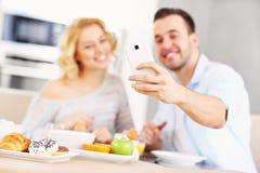 Couples heureux mangeant le petit déjeuner et prenant le selfie Images stock