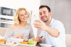 Couples heureux mangeant le petit déjeuner et prenant le selfie Photographie stock libre de droits