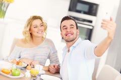Couples heureux mangeant le petit déjeuner et prenant le selfie Photos libres de droits