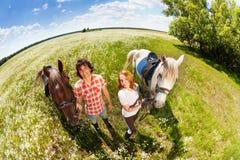 Couples heureux marchant avec leurs chevaux de race Photographie stock