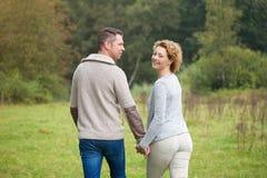 Couples heureux marchant dans la campagne photo stock