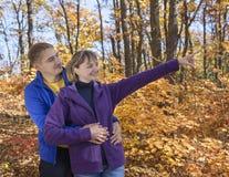 Couples heureux marchant en stationnement d'automne Images stock