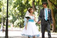 Couples heureux marchant et se souriant sur le parc de fond Photos libres de droits