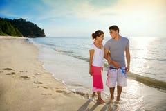 Couples heureux marchant le long de la plage Photographie stock