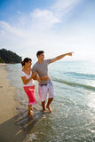 Couples heureux marchant le long de la plage Photographie stock