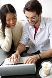 Couples heureux mignons travaillant sur l'ordinateur portable Photos stock