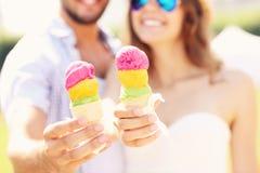 Couples heureux montrant des cornets de crème glacée Image stock