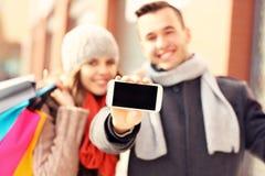 Couples heureux montrant le smartphone tout en faisant des emplettes Image stock