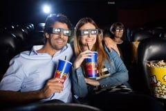 Couples heureux observant le film 3D dans le théâtre Photographie stock