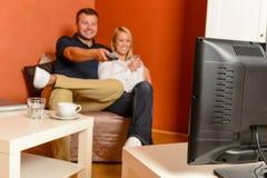 Couples heureux observant les canaux changeants de soirée de TV Photographie stock