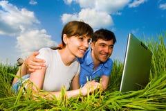 Couples heureux occasionnels sur un ordinateur portable à l'extérieur. Photographie stock libre de droits