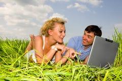 Couples heureux occasionnels sur un ordinateur portable à l'extérieur Image stock
