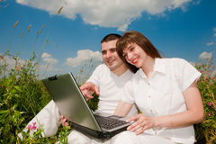 Couples heureux occasionnels sur un ordinateur portable à l'extérieur Images libres de droits